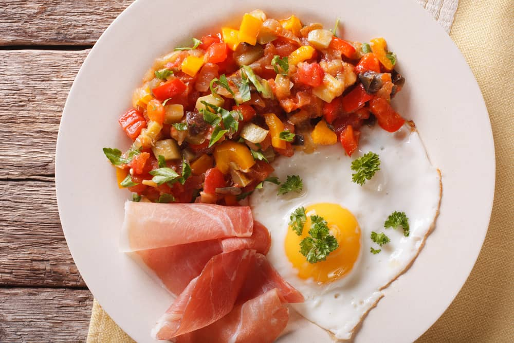 plate of pisto fried eggs and jamon