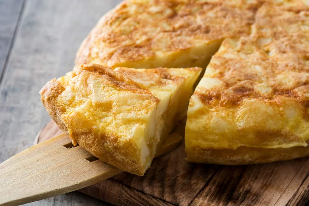 sliced spanish tortilla served on a wooden platter