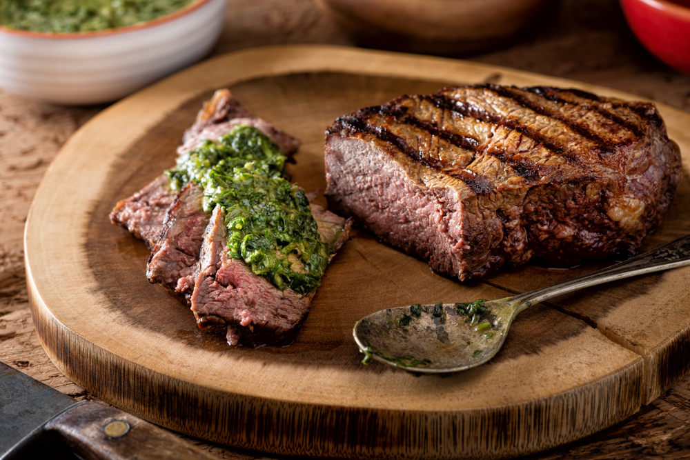 Sliced Asado Steak from Argentina with chimichurri served on a cutting board
