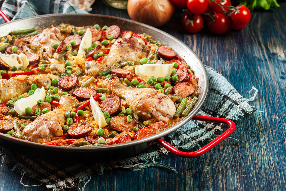 Spanish paella with pollo and chorizo served in traditional paella pan