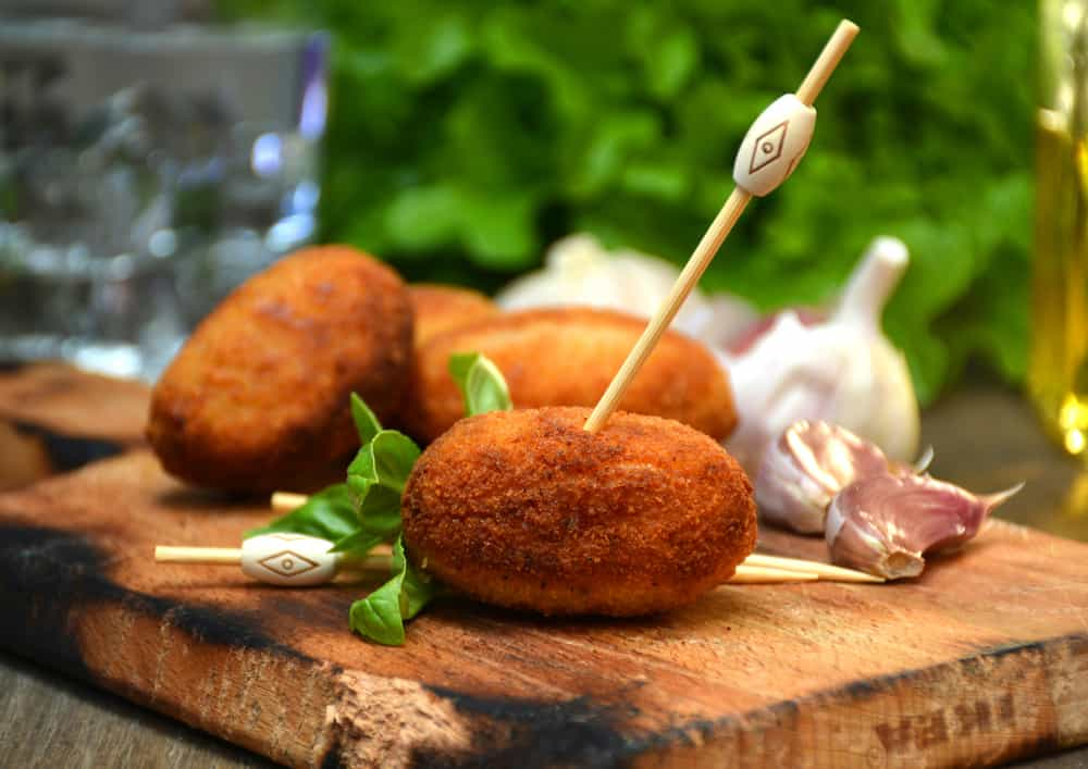 Spanish Croquetas on wood cutting board with toothpick