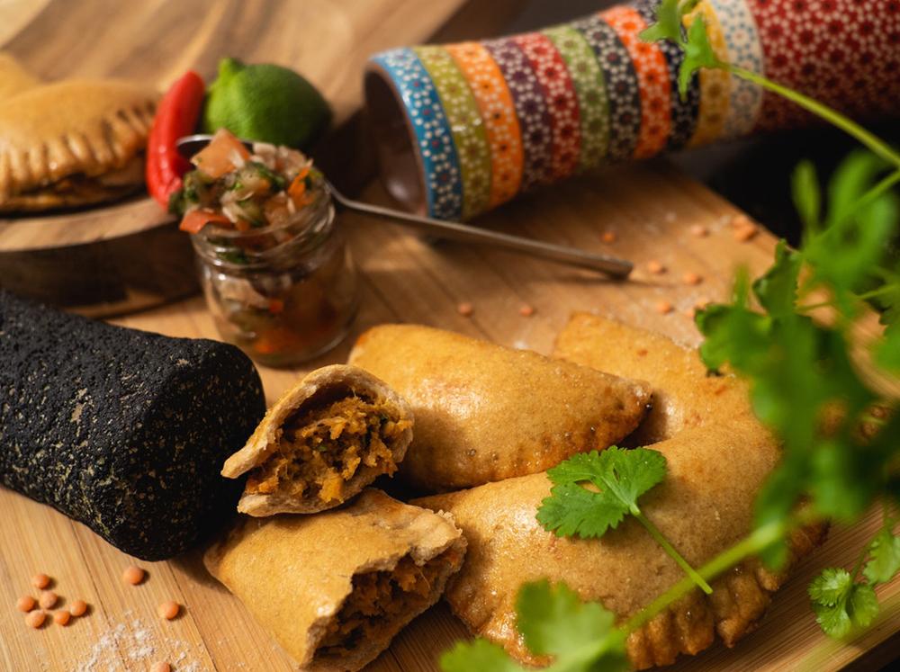 Empanadas cut in half with sauce on cutting board