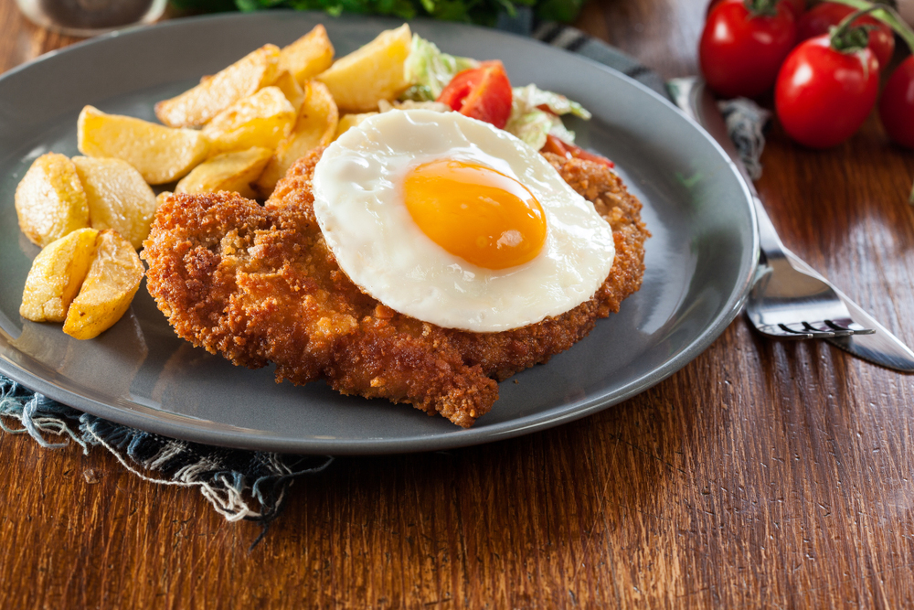 Dish of Milanesa breaded steak, egg, and french fries