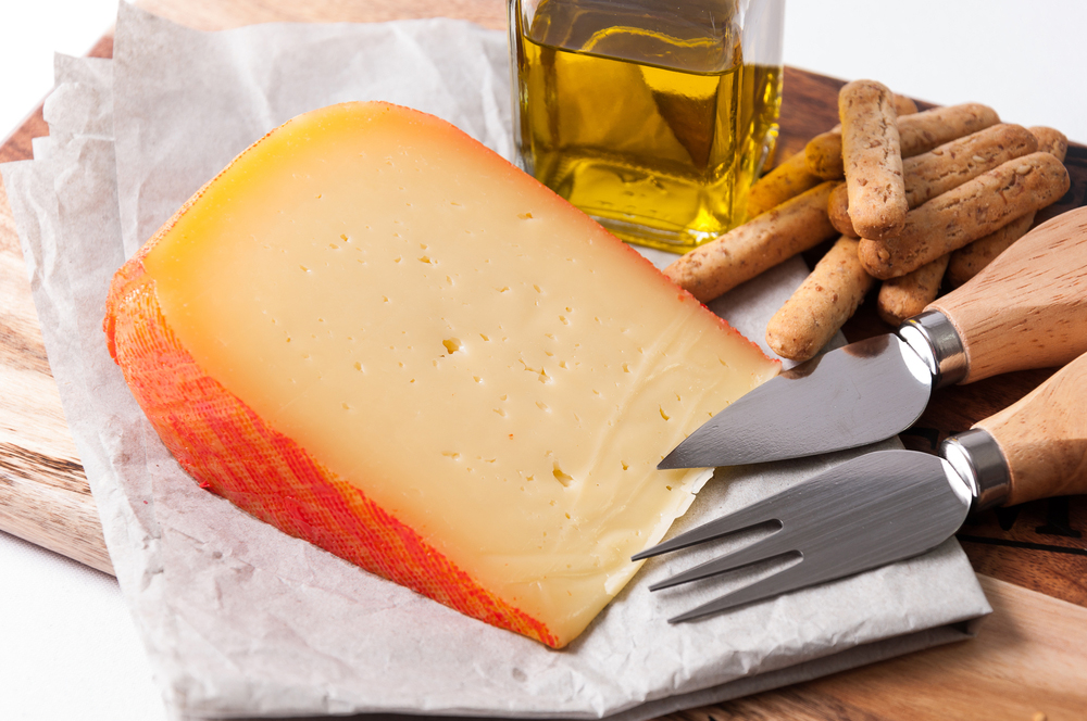 Mahón Cheese wedges with knife, fork and glass jar of olive oil