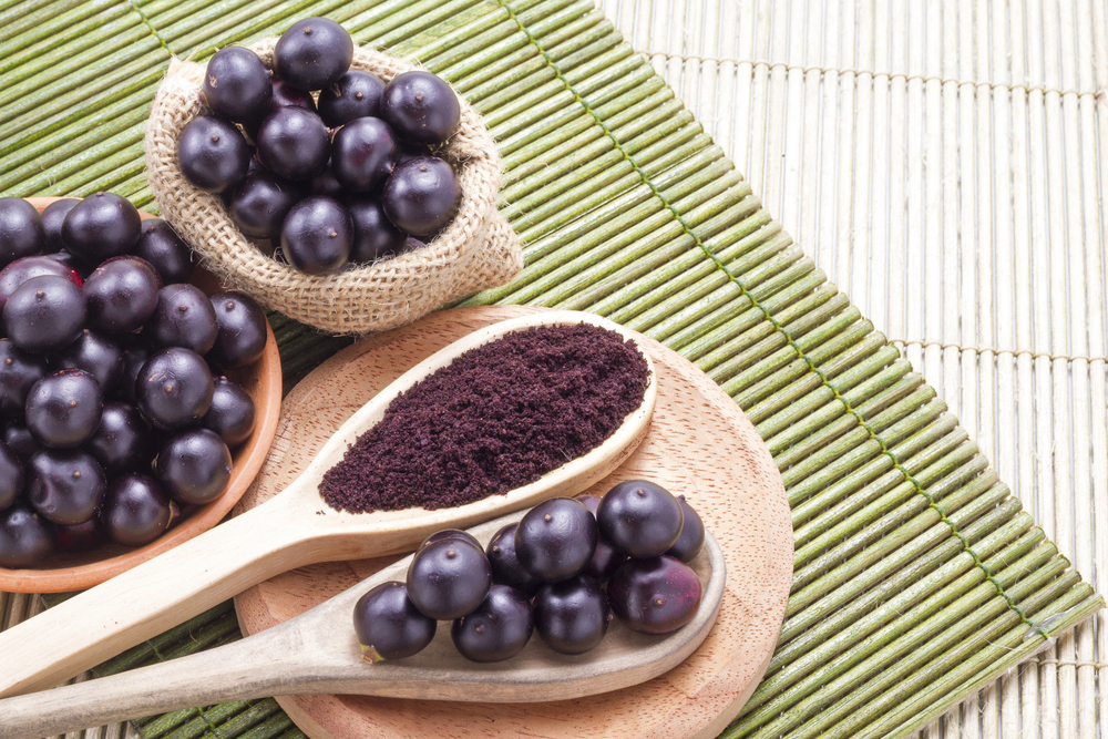 Acai berries and acas powder on wooden spoons