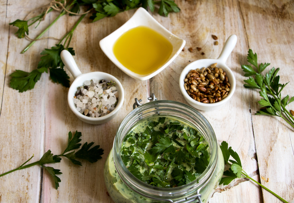 Ingredients to make chimichurri sauce, parsley, olive oil, salt, pepper, garlic