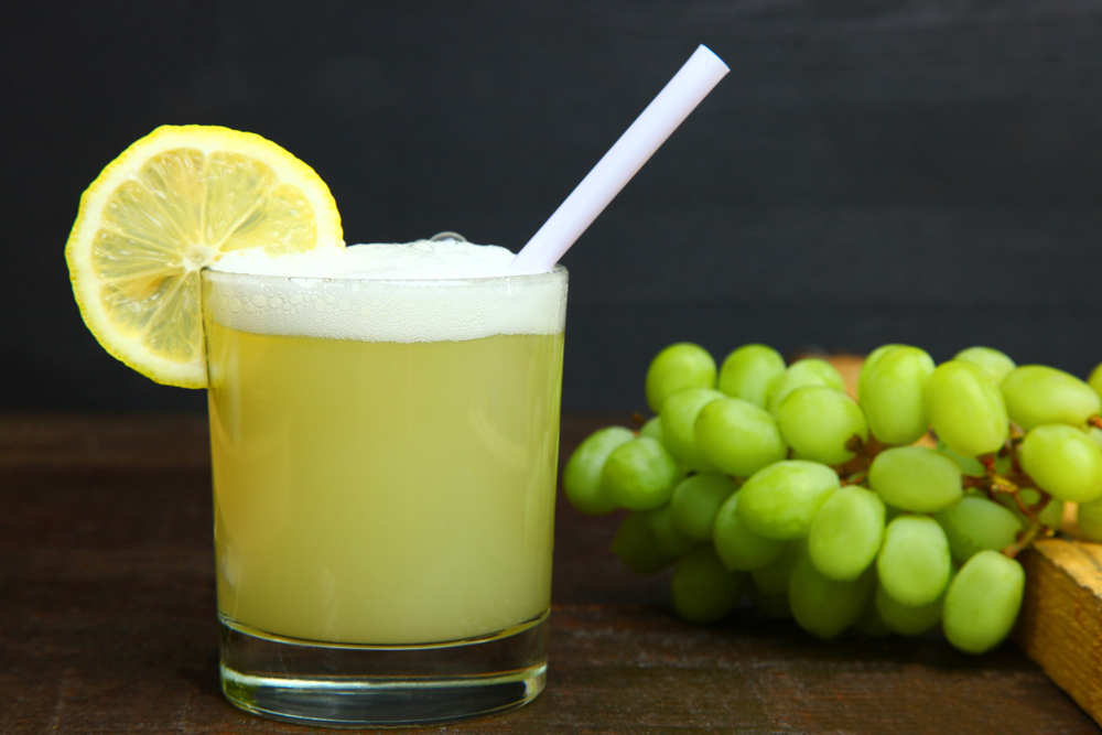 glass of Pisco sour drink with lime and straw