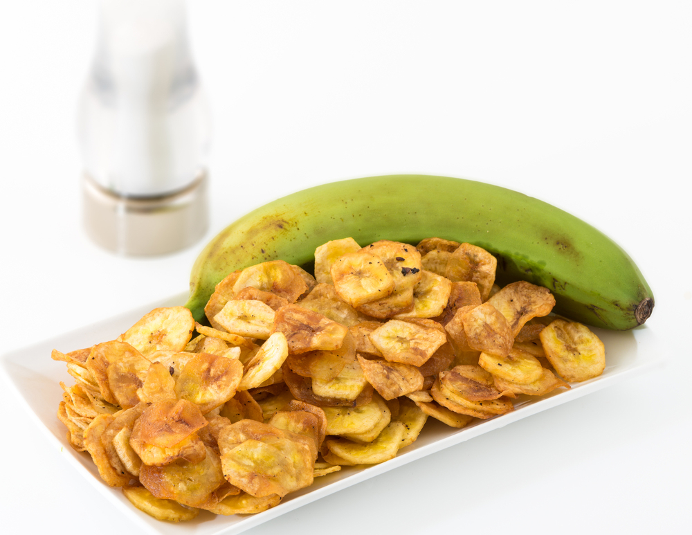side dish of plantain chips and unripened green plantain with salt shaker