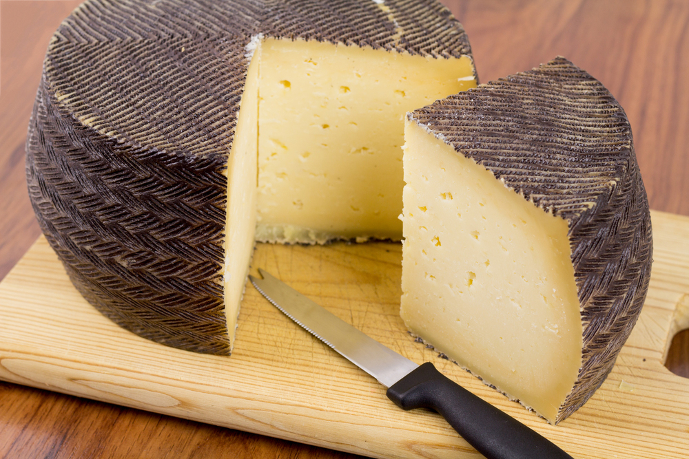 sliced queso manchego wheel on wooden cutting board