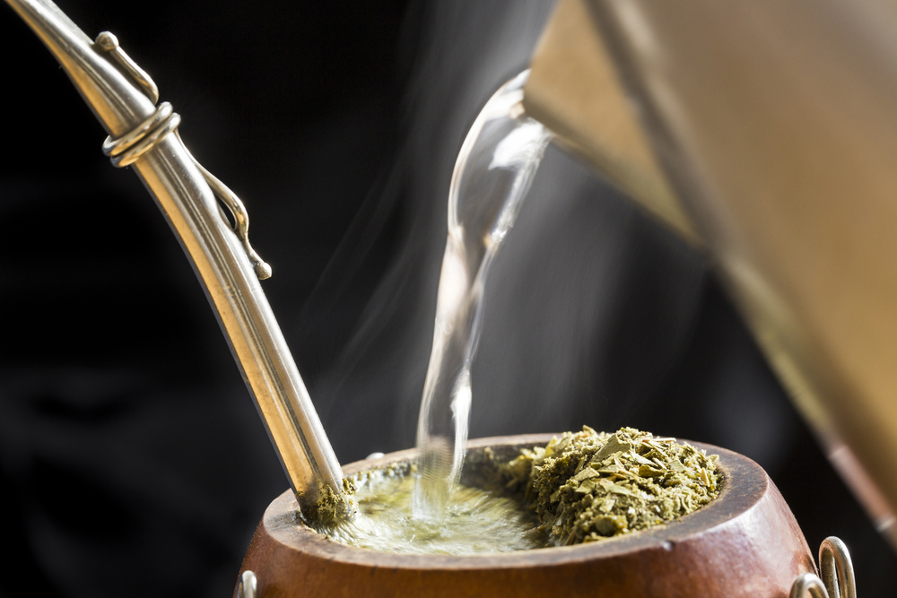 hot water pouring from pitcher into Yerba mate gourd
