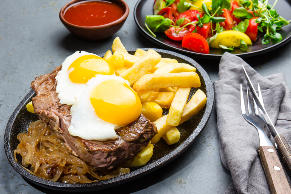 Chilean Plate of Chorrillana consisting of French fries, steak, fried eggs and fried onions.