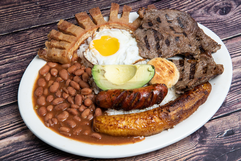 Plate of Colombian Bandeja Paisa consisting of chicharron, sausage, beans, eggs, fried plantains