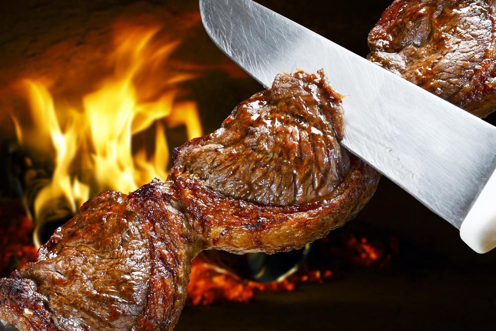 Brazilian Picanha steak on a skewer being cut