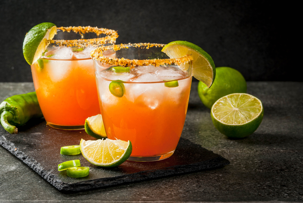 Two glasses of Michelada Latin Drink with limes