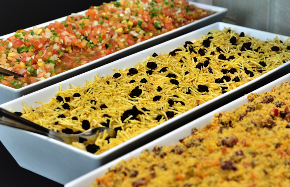 Salpicão de Frango served along with farofa in white trays