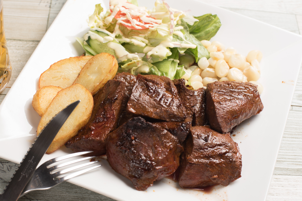 Anticuchos Beef Hearts served on a white plate with boiled potatoes, white corn and salad