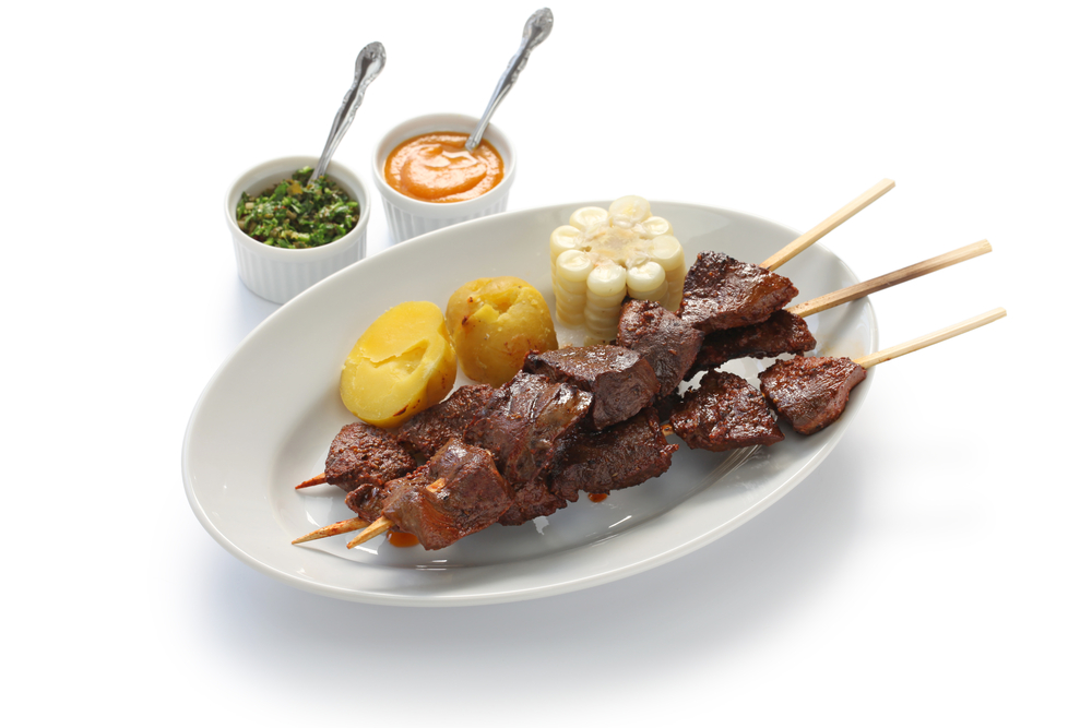 Peruvian Anticuchos Dish served on white plate with white corn, potato and Peruvian aji sauce