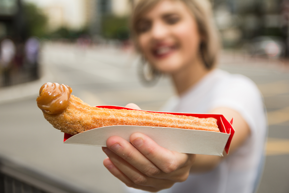 Brazilian Churro with girl holding it into camera