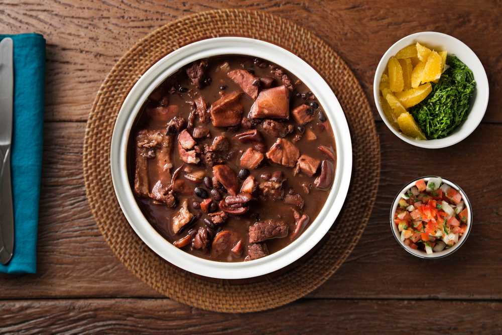 Brazilian Feijoada dish served in a bowl with side dishes