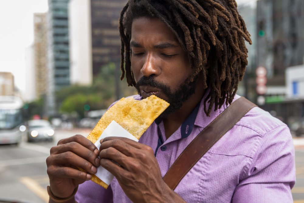 Brazilian Man eating pastel Brazilian street food
