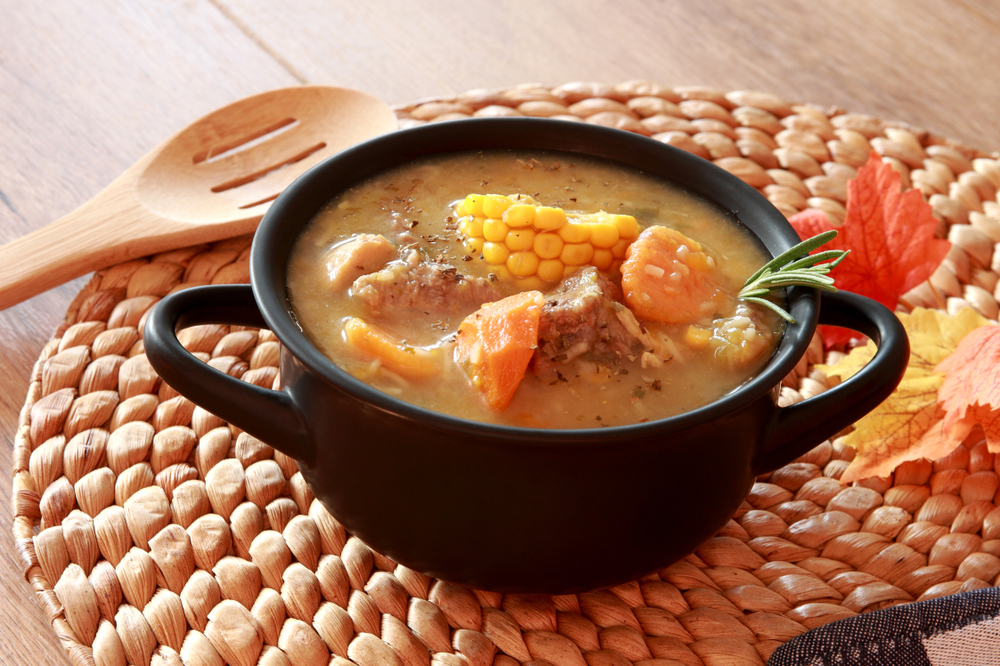 Colombian Cuisine sancocho served in black pot on table