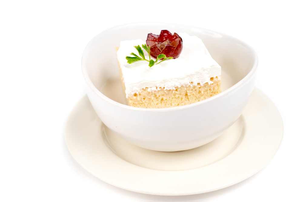 Colombian Ttes Leche Cake served in a white bowl on a white background