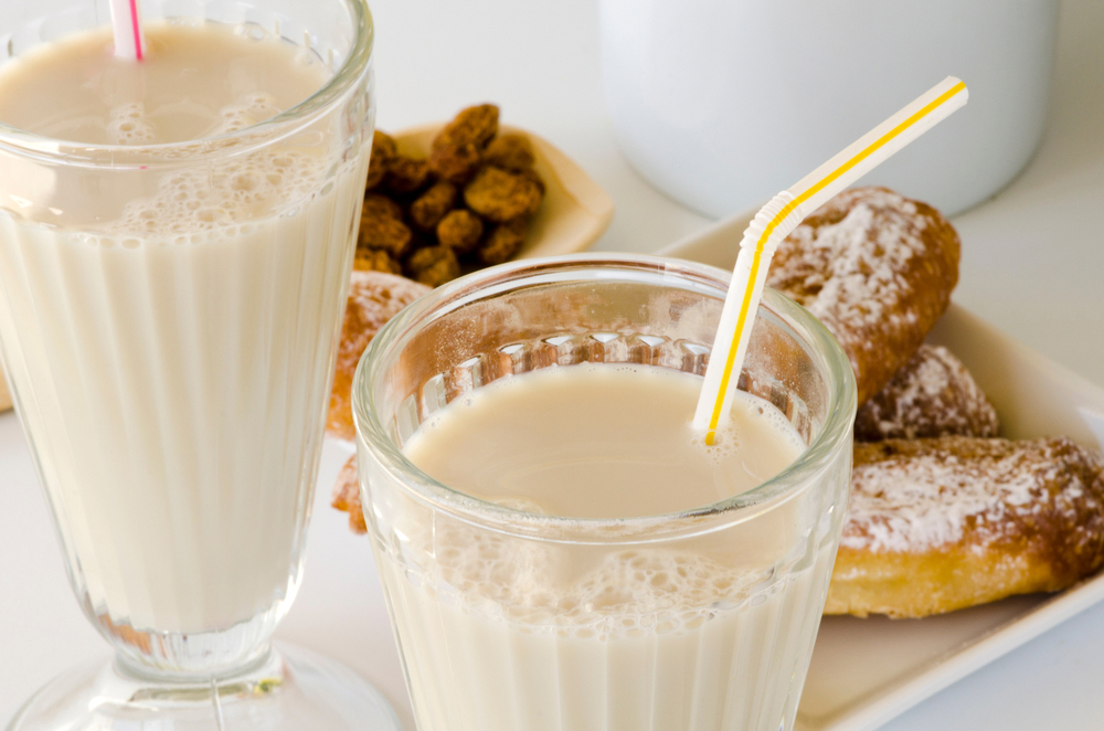Two glasses of Spanish Horchata de Chufa with pastry and bowl of tiger nuts