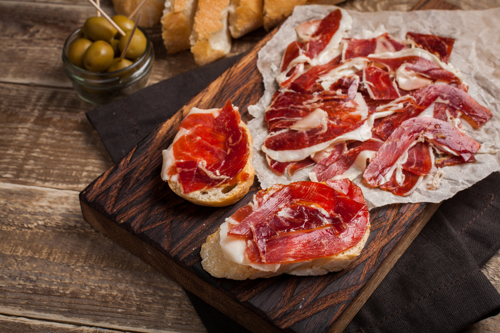 Cutting board of sliced Jason iberico on bread with olives and bread