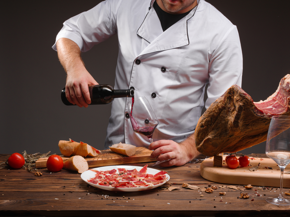 Chef pouring glass of red wine with Jason iberico, tomato and spanish olive oil on wooden table