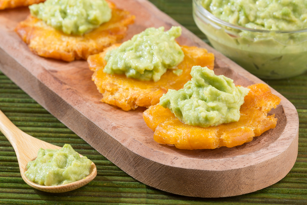 Patacones with green sauce on wooden cutting board