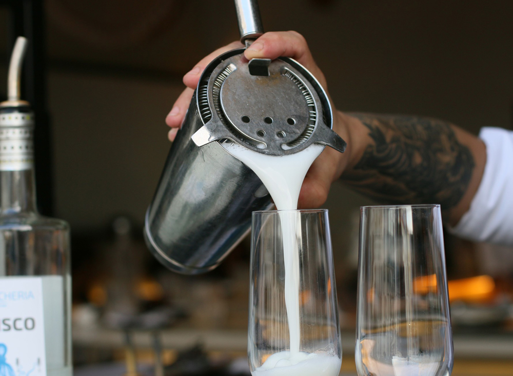 Pisco cocktail being poured out of shaker