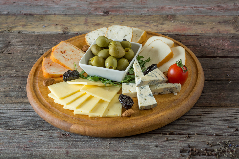 Spanish Chees and olive antipasto plate on round cutting board