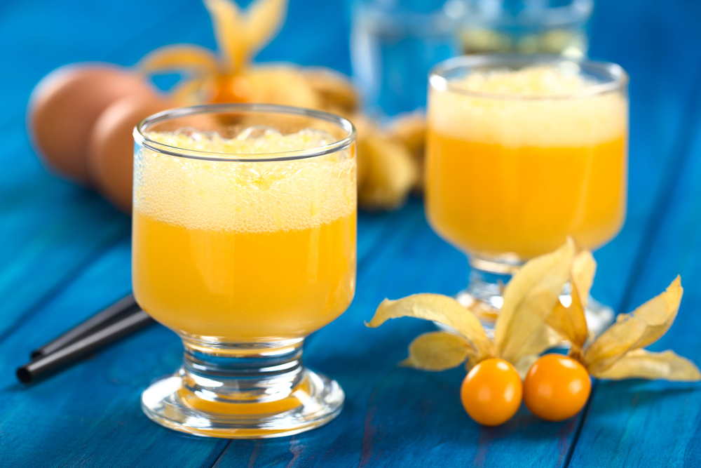 Two glasses of Aguaymanto (Physalis) Sour on blue table