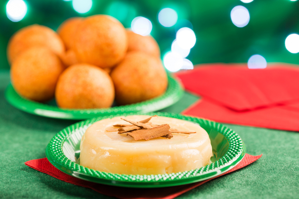 Plates of Colombian Christmas Food of Bunuelos and Natilla on green tablecloth