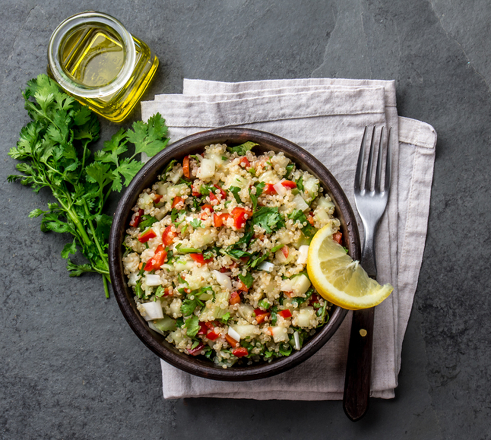 Plate Peruvian Quinoa Salad with dressing on a dark slate table