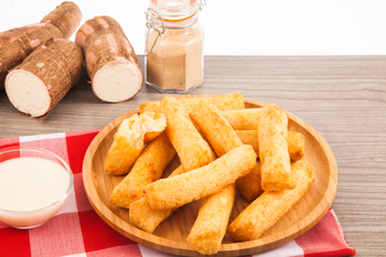 Yuca Fries served on a plate with Cassava in the background