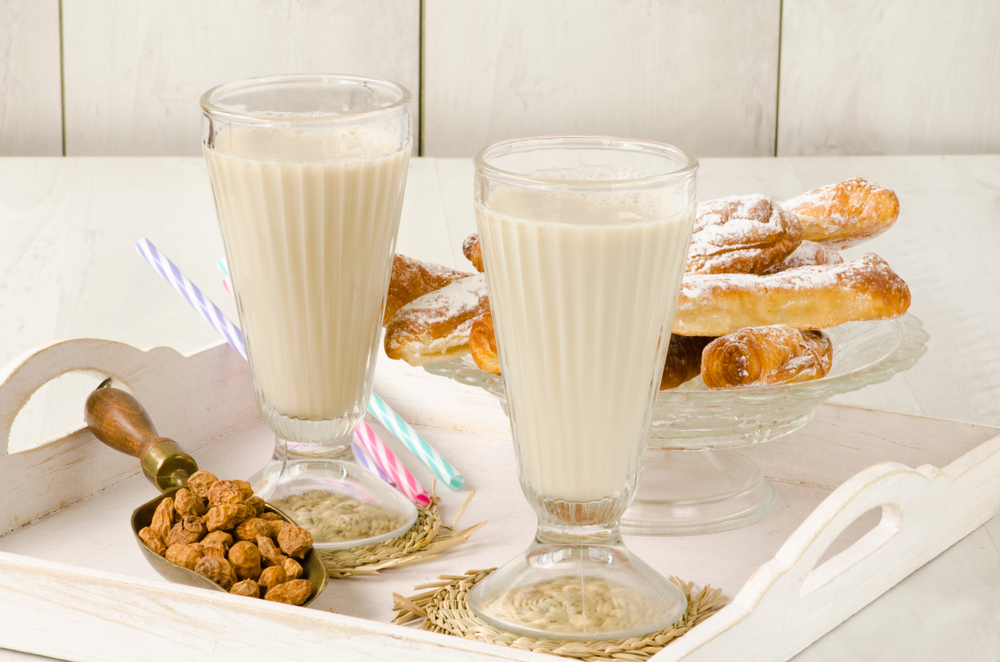Spanish Horchata Drink in tall glasses on tray with Spanish bread and nuts