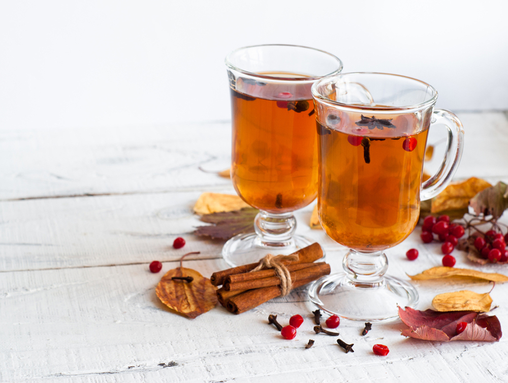 Two glasses of Te Piteado on white background and white table with cinnamon and spices