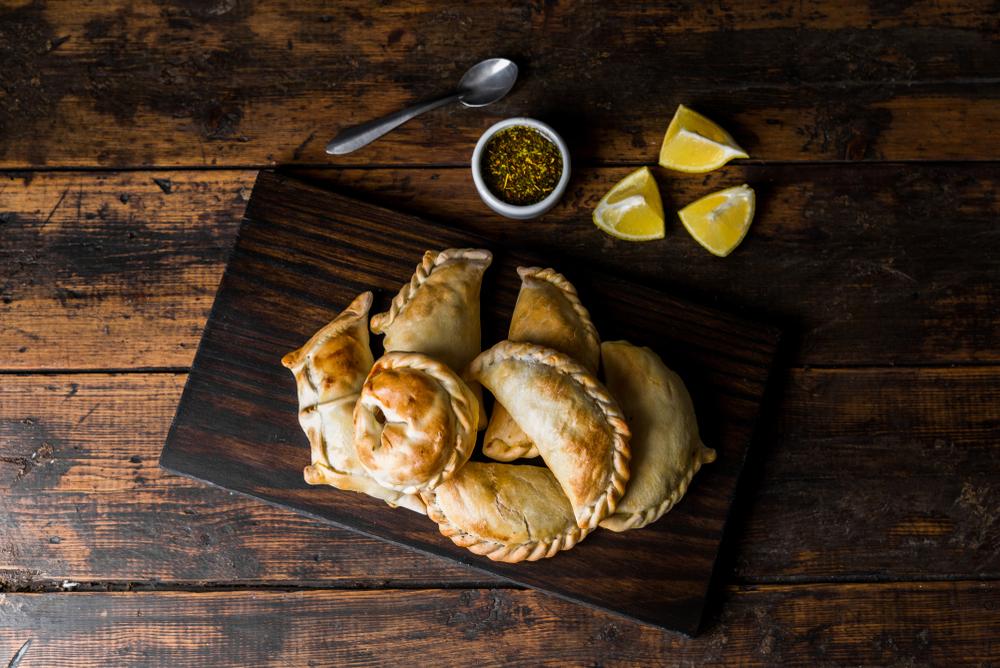 Argentinian Christmas Empanadas on wood platter on table
