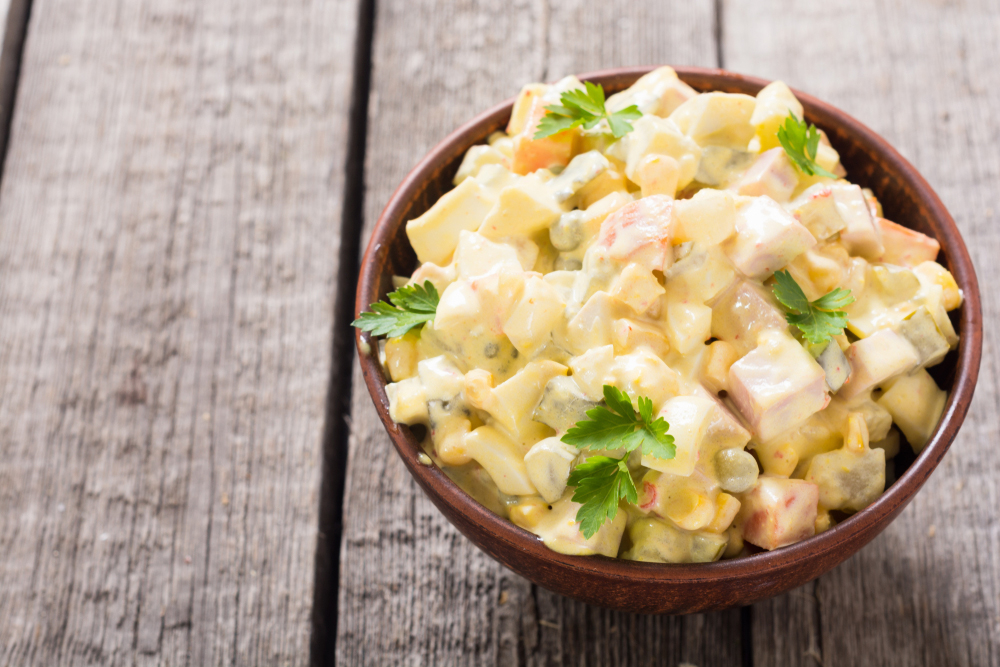 Argentinian Russian salad in bowl on wooden table