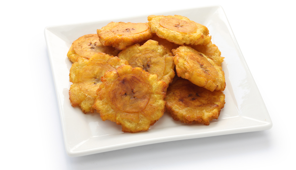 Cuban Christmas tostones, fried green plantain chips on white plate