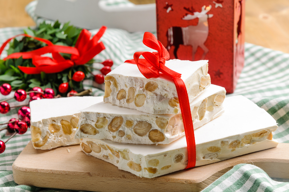 Cuban Christmas alicante turron nougat candy on cutting board tied with red ribbon