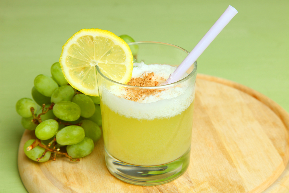 Pisco sour with lemon wedge on wooden platter with green grapes