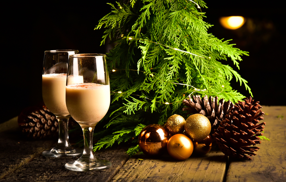 Puerto Rican Coquito in stemmed glass with Christmas decorations