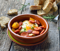 Spanish chorizo sausage with fried egg and potatoes served in a terra cotta cazuela dish