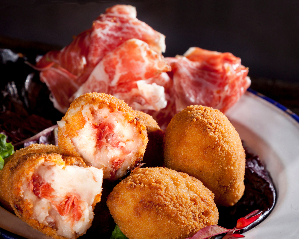 Spanish Christmas tapas croquetas de jamon with slices of Jamon Serrano