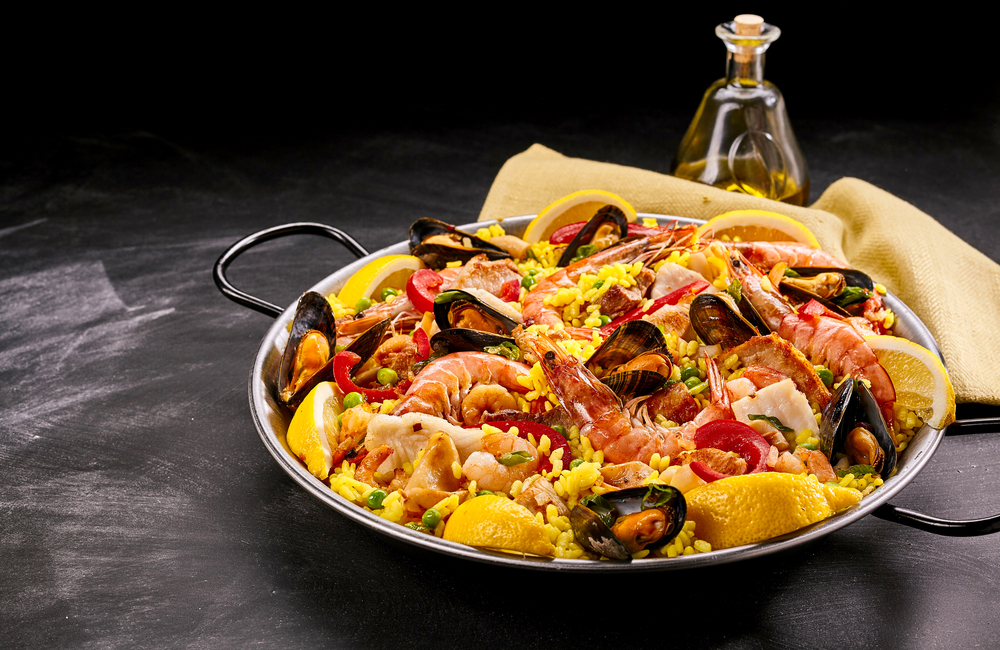 Spanish Seafood Paella Rice Dish with Fresh Shellfish Served with Lemon Wedges in Pan on Smudged Chalkboard Background with Oil and Napkin