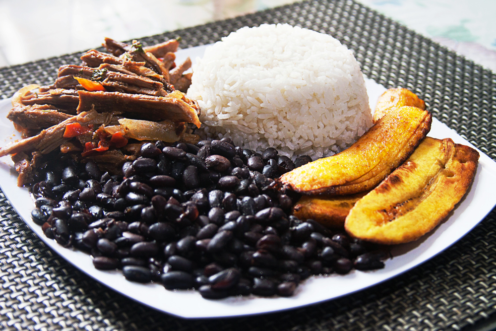 Venezuelan Pabellon Criollo, White Rice, Black beans, Fried plantains, and Shredded beef on a plate