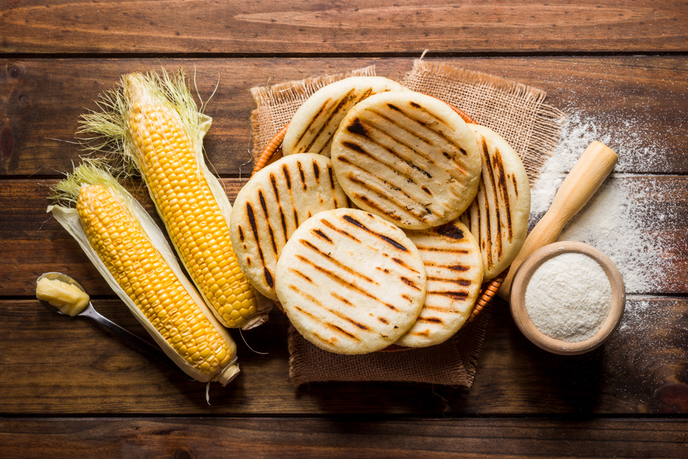Venezuelan arepas with corn and flour on table