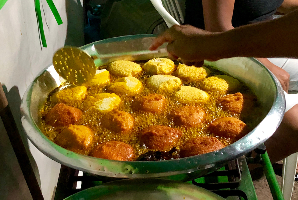 Frying acaraje fritters in palm with boiling palm oil